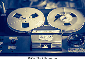 Vintage reel-to-reel tape recorder with a few rolls of tape