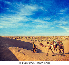 Vintage retro hipster style travel image of Rajasthan travel background - India cameleer (camel driver) with camels in dunes of Thar desert with grunge texture overlaid. Jaisalmer, Rajasthan, India