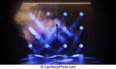 Vintage retro microphone on empty stage against a black background with blue lighting. Microphone stay in a smoke. Music instrument concept.