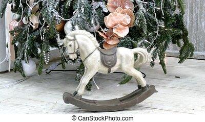 Vintage rocking horse on christmas tree background