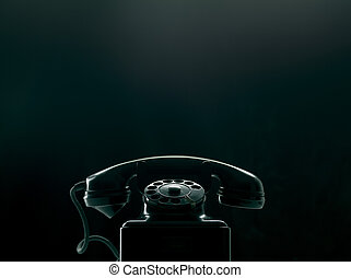 Vintage rotary dial phone on black background, low key silhouette