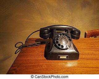 vintage black analog rotary dial telephone on a desk