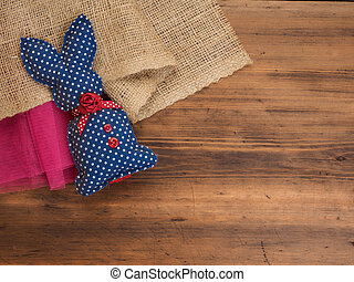Vintage, rustic background with a toy rabbit on a background of burlap and old wooden table. Top view.