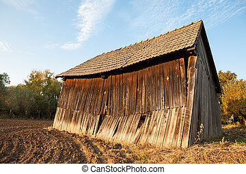 An old wooden farm building barn in the middle of a field