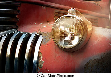 Vintage rusty red truck car with a new headlight in the sunshine, soft focus