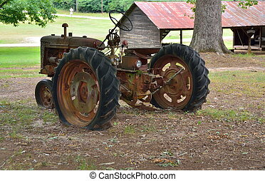 Vintage Rusty Tractor - Rusty old tractor at farm in rural...