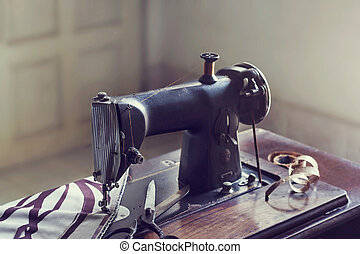 vintage sewing machine with fabric and scissor in the room,...