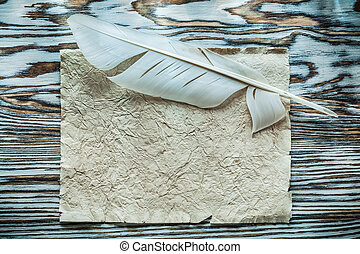 Vintage sheet of paper feather on wooden board