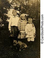 Vintage Siblings - Three siblings in a garden portrait with...