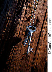 Old antique skeleton keys hanging from metal chain against distressed wood surface