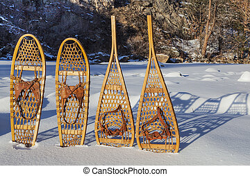 vintage Bear Paw and Huron snowshoes cast shadow in snow, Poudre River Canyon near Fort Collins, Colorado