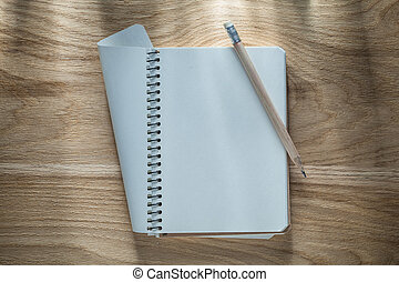 Vintage spiral blank notepad pencil on wooden board