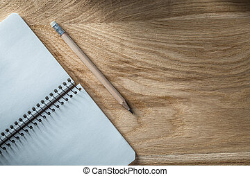 Vintage spiral notebook pencil on wooden board top view