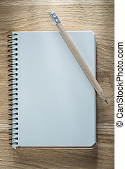 Vintage spiral notepad pencil on wooden board