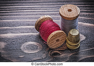 Vintage spools of thread thimbles on wooden board handicraft...