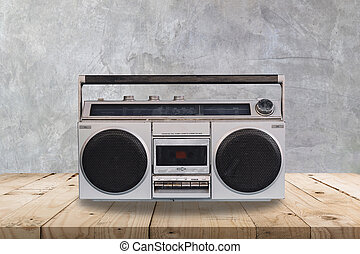 Vintage stereo on wooden table and concrete wall texture and background.
