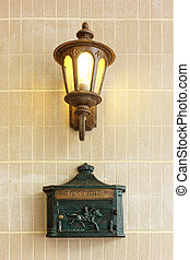 Vintage street lamp with letter box on wall