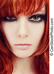 Vintage style close-up portrait of young beautiful green-eyed girl with red hair and stylish smoky eyes makeup