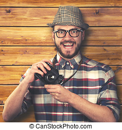 vintage style happy smiling hipster with retro camera in hands