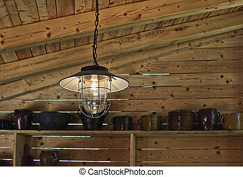 Vintage style lamp hanging inside a wooden barn