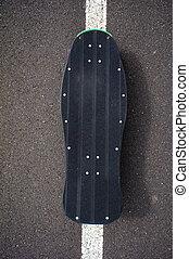 Vintage Style Longboard Black Skateboard on an Empty Asphalt...