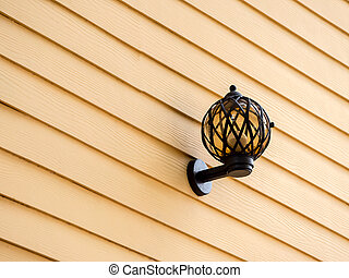 vintage style outside lamp on yellow wooden wall.