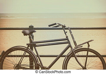 Vintage styled image of the Dutch beach with a black retro bicycle in Scheveningen