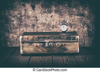 Vintage suitcase and a clock on a wooden floor