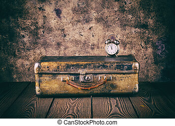 Vintage suitcase and a clock on wooden floor
