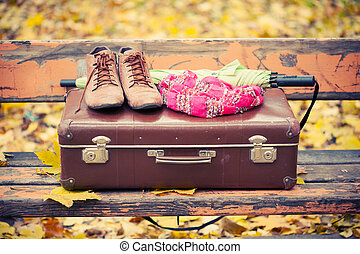 vintage suitcase, scarf, boots and umbrella on bench in ...