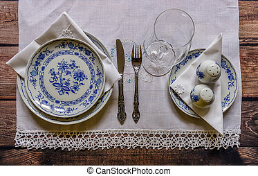 Vintage table setting with china and silver cutlery on the wooden background