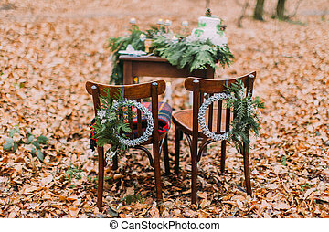 Vintage table with cake and candles in the autumn forest. Chairs on foreground