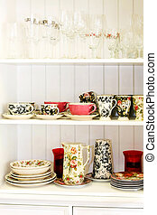 Interior of kitchen cabinet with vintage tableware