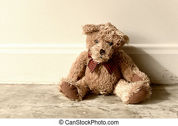 Vintage teddy bear alone in room