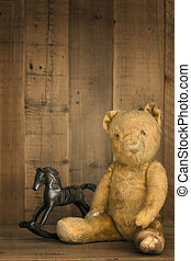 Vintage teddy bear with rocking horse, on wooden shelf.