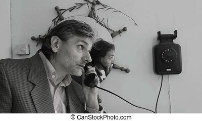 vintage Telephone man - 1970 telephone, man hangs up a...