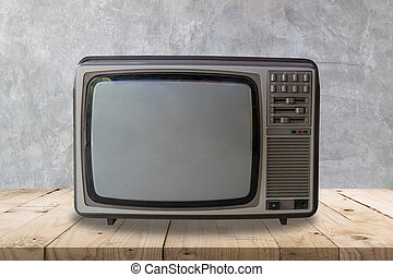 Vintage television on wooden table and cement wall texture and background.