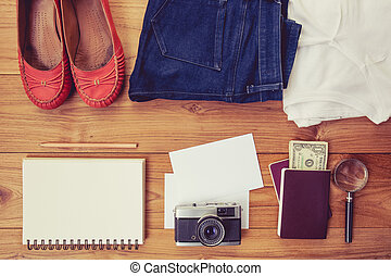 Vintage tone of Outfit of traveler, student, teenager, young woman. Overhead of essentials for a person. Different objects on wooden background.