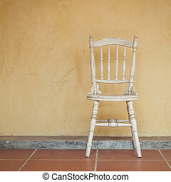 Vintage tone of white Vintage chair near yellow old wall