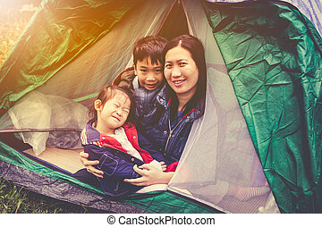 Vintage tone photo of happy family looking at camera on camping trip.