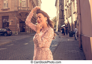 Vintage toning portrait of awesome cheerful woman at the street during a sunny morning
