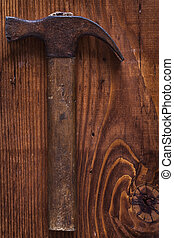 vintage tool claw hammer on old wooden board