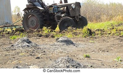 Vintage tractor plows agricultural field to protect against ...