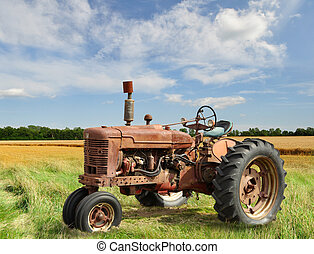 vintage tractor - red old rusty tractor in a field
