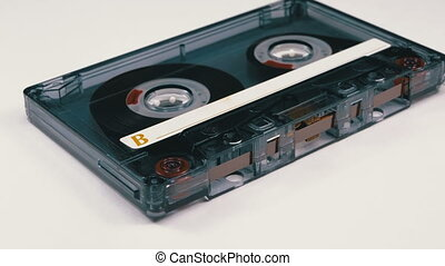 Vintage Transparent Audio Cassette Rotates on White Background. Retro tape cassette with a blank label. Old music. Close-up.