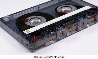 Vintage Transparent Audio Cassette Rotates on White Background