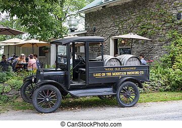 Vintage truck stands with barrels of beer for a pub