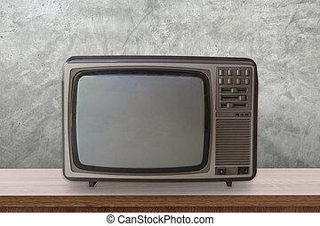 Vintage TV box on wooden table and cement wall background.