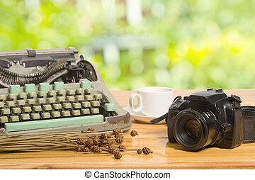 vintage typewriter and camera on green bright blur background