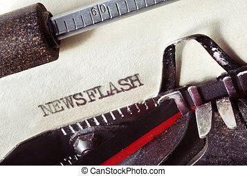 """Vintage typewriter with aged paper, showing the word """"Newsflash"""". Close-up view, with lots of dust and great paper texture."""